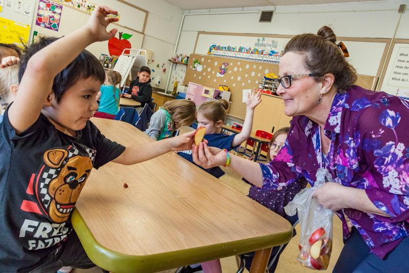 teaching handing a student an apple